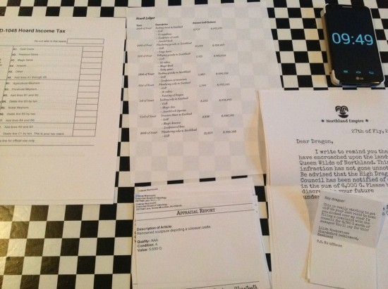 Printed out pages of dragon tax documents organized on a table, in the same layout as the computer game, next to a smartphone displaying 9:49.